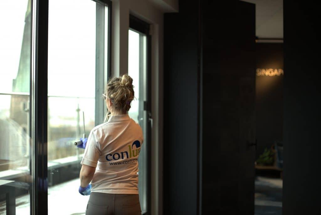 Conluo medarbeider vasker vinduer