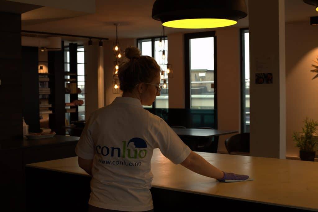 Conluo medarbeider rengjør bord